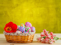 Brightly colored eggs with flowers in a wicker basket Stock Image