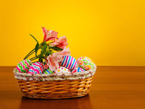 Brightly colored eggs with flowers in a wicker basket Stock Photos