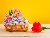 Brightly colored eggs with flowers in a wicker basket Royalty Free Stock Photos