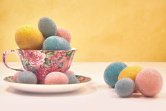 Brightly colored eggs in tea cup Royalty Free Stock Photography