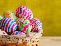 Brightly colored eggs in a wicker basket Royalty Free Stock Images