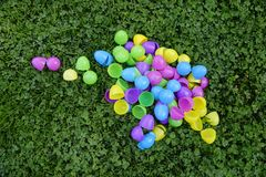 Big Pile of Plastic Eggs. Brightly colored empty plastic eggs in a large pile amongst green clover. Close up Stock Photography