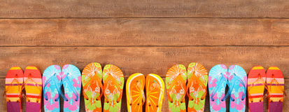 Brightly colored flip-flops on wood. Deck stock image