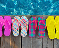 Brightly colored flip-flops on wooden background Stock Photography