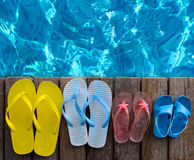 Brightly colored flip-flops on wooden background near the pool Stock Photos