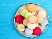 Brightly colored French macarons. Traditional brightly colored French macaroons on a hand-made plate, set on a blue wooden board, top view Royalty Free Stock Photography