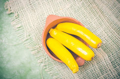 Brightly colored fresh zucchinis in terracota bowl Royalty Free Stock Photos