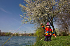 Brightly colored girl pretends to be fishing under a blossoming tree Stock Images
