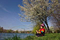 Brightly colored girl pretends to be fishing under a blossoming tree Stock Image