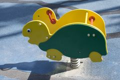 A brightly colored green and yellow rocking turtle at a public playground. Activity toy in the park, kindergarten or school yard. A brightly colored green and royalty free stock photography
