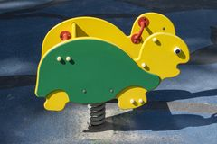A brightly colored green and yellow rocking turtle at a public playground. Activity toy in the park or school yard. A brightly colored green and yellow rocking stock photos