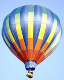 Brightly Colored Hot Air Balloon. A rainbow colored hot-air balloon drifts through a clear blue sky Stock Images