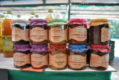 Brightly colored jars with home-made jam on a market counter in France. A colorful display of jams Stock Image