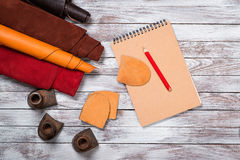 Brightly colored leather in rolls, working tools, shoe lasts, notebook with pencil on white background. Leather craft. royalty free stock photography