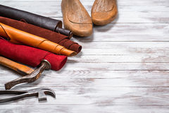 Brightly colored leather in rolls, working tools and shoe lasts on white wooden background. Leather craft. Copy space. royalty free stock images