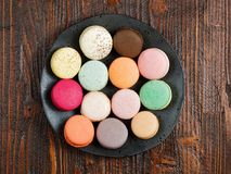 Brightly colored macaroons on a hand-made plate. Set on a rustic brown wooden board Royalty Free Stock Photography