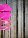 Brightly colored pink flip-flops of a mother and daughter on woo Stock Photos