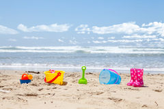 Brightly colored plastic beach toys on the beach Stock Photos