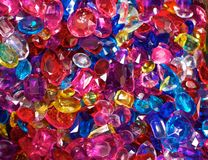 Brightly Colored Plastic Jewels. A field of brightly colored plastic jewels which are pink, red, blue and yellow in color Stock Photography
