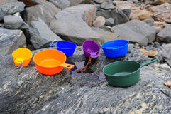 Brightly-colored Plastic Scoops on Gray Rocks Stock Photography