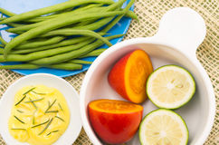 Brightly colored Plates with green beans, butter Stock Photo