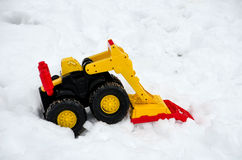 Front end loader in the snow. Brightly colored sand toy double as a fun snow mover royalty free stock image