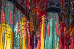 Brightly colored and saturated boho background with layers of fabrics and tassels and net stock photos