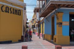 Brightly Colored Side Street in Santa Marta. Santa Marta, Columbia-- April 22, 2018. Photo of pedestrians on a brightly colored side street in Santa Marta Royalty Free Stock Photos