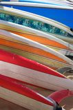 Brightly Colored Surfboards Laying on the Sand. A row of brightly colored renal surfboards laying on the sand in Hawaii Royalty Free Stock Photos