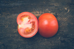 Brightly colored tomato cut in half with one side Royalty Free Stock Photography