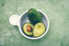 Brightly colored two avocados in a white bowl with Royalty Free Stock Photos