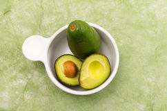 Brightly colored two avocados in a white bowl with Stock Photos