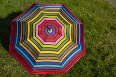 Brightly Colored Umbrella on Green Grass. Brightly colored umbrella with geometrical pattern, expanded, resting on green grass on a sunny day Royalty Free Stock Images