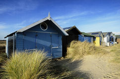 Brightly Coloured Beach Huts. Beach huts in sand dunes at Mudeford Spit on Hengistbury Head near Christchurch in Dorset Stock Photo