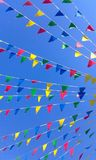 Brightly coloured bunting against a blue sky stock photos