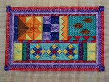 Brightly coloured canvas-work embroidery. Brightly coloured rectangular embroidery on canvas. Geometric shapes have been created using a straight stitch stock photography