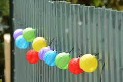 Brightly coloured colored balls. Hanging from a fence. Purple, mauve blue green red and yellow, like balloons but made from plastic Stock Photos