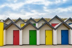 Brightly coloured front doors of four modern beach huts. Showing zigzag roof line royalty free stock image