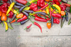 Brightly Coloured Mixed Chillis on Weathered Wooden Table Royalty Free Stock Images