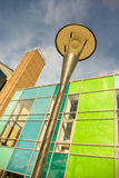 Brightly coloured modern building and streetlamp. At angle against blue sky Royalty Free Stock Photo