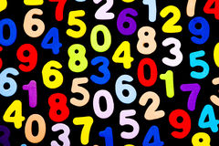 Brightly coloured numbers on black background Royalty Free Stock Images