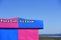Brightly coloured pink and blue Ice cream and fish & chips and donuts kiosk on Southend on Sea royalty free stock photos