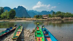 Colorful Pirogues on Nam Song River, Laos. Brightly coloured Pirogues on the banks of the Nam Song River with impressive limestone mountains in the background stock images