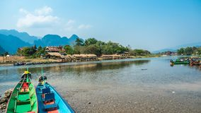 Colorful Pirogues on Nam Song River, Laos. Brightly coloured Pirogues on the banks of the Nam Song River with impressive limestone mountains in the background royalty free stock image