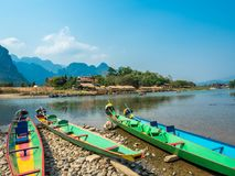 Colorful Pirogues on Nam Song River, Laos. Brightly coloured Pirogues on the banks of the Nam Song River with impressive limestone mountains in the background stock photo