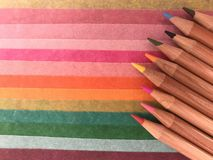 Coloured pencils on sheets of coloured paper. Brightly coloured sharpened crayons in a row on a multicoloured, striped, paper background stock photography