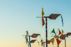 Brightly coloured windmills. An assortment of hand-crafted brightly coloured windmills against a clear sky Royalty Free Stock Images