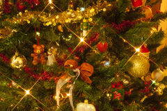 Brightly decorated Christmas tree. Ornaments hanging on the branches of the Christmas tree, with stars of light and reflections on Christmas balls. There is also Stock Photography