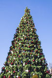 Brightly Decorated New Year tree at street with blue sky Royalty Free Stock Photography