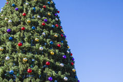 Brightly Decorated New Year tree at street with blue sky Stock Images